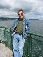 Author Bruce Fergusson standing at the railing of a ferry.